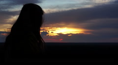 Female silhouette at sunset, woman looking at orange sky, wind playing with hair Stock Footage