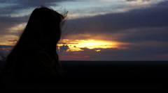 Woman with long hair looking at beautiful sunset or sunrise, feeling of freedom Stock Footage
