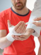 Doctor bandaging the hand of a sport man after an accident Stock Photos