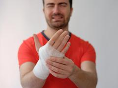 Sport man with bandages medication on his hand suffering after a sport injury Stock Photos