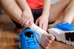Sportsman massaging his injured ankle after a sport accident Stock Photos
