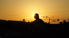 Person sitting on the roof during a golden sunset. Hand in sunset. Stock Footage