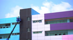 Painter in the cradle of skylift paints the wall of an old building Stock Footage