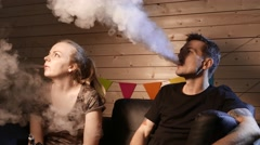 A group of people vaping, inhaling and exhaling large clouds of smoke and having Stock Footage