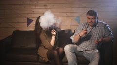 A couple vaping, inhaling and exhaling large clouds of smoke and having fun - stock footage