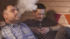A group of people vaping, inhaling and exhaling large clouds of smoke and having - stock footage