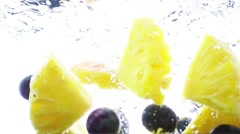 Cut pineapple and grapes falling into water in slow motion. Stock Footage