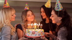 Young girls look at cake and make a wish Stock Footage
