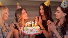 The girl in the birthday makes a wish and blows out the candles on the cake Stock Footage