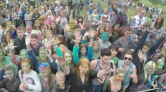 Happy crowd on Holi Festival waving hands, aerial view Stock Footage
