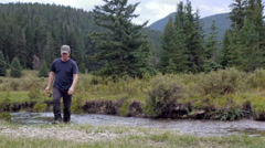 A man with a fishing rod walks past the camera away from a river Stock Footage