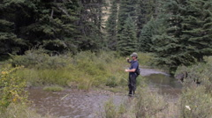 A fisherman reels in a fish with his fly rod in a river in the wilderness -wide Stock Footage