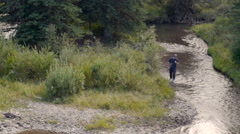 A man walking along a stream or river with a fishing pole in his hand Stock Footage
