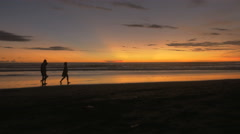 Silhouettes of people walking along the beach during sunset in Bali Stock Footage