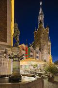 Side view of the old town hall of Aachen, Germany with night blue sky. A cafe Stock Photos