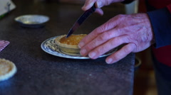 4K aged caucasian man's hand cuts up bakewell tarts/cakes on pretty plate Stock Footage