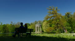 4K Couple sitting on bench garden park Apollo Temple Nymphenburg Park in Munich - stock footage