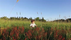 Toddler sitting on the grass and playing around. - stock footage