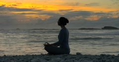Young healthy woman practising yoga meditation at sunrise / sunset Stock Footage