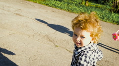Carefree childhood. Cute curly little boy running on the track. He is holding a Stock Footage