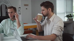 Two young professional businessmen are working in a light and modern open plan Stock Footage