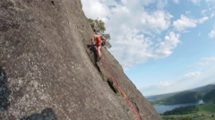 Man Rock Climber Lead Climbing Steep Mountain Cliff on Sunny Day Stock Footage