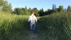 Walking in the trail with the tall grass. - stock footage