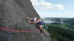 Man Rock Climbing on Top Rope Up Mountain Overlooking Valley with Lake Stock Footage