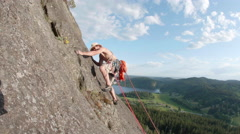 Man Rock Climber Lead Climbing Up Mountain on Sunny Day Stock Footage