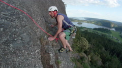 Rock Climber Following Multi-Pitch Up Mountain Cliff with Scenic View of Lake Stock Footage