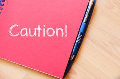 Caution write on notebook - stock photo