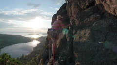 Rock Climber on Mountain Cliff with Amazing Sunset View of Ocean and Lake Stock Footage