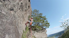 Rock Climber on Sunny Day with Blue Sky Jumping and Rappeling Down Mountain Stock Footage