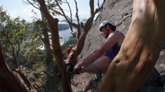 Rock Climber Putting on Shoes on Mountain with Ocean View Stock Footage