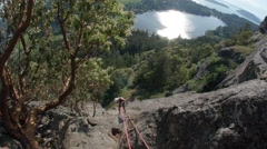 Top Angle of Rock Climber Rappelling Down Mountain with Ocean View Stock Footage