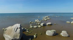 4K. Flight and takeoff over the sea with stones standing in the water, aerial. Stock Footage