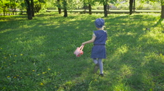 Little girl running in the park. It accelerates urban pigeons, for her fun Arkistovideo