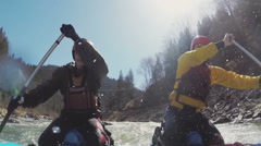 Two people paddling inflatable boat down rapids. Slow motion - stock footage