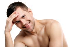 Attractive naked man is evincing his shame - stock photo