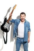 Angry male guitarist expressing negative emotions - stock photo
