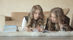 Twin sisters leafed through the book lying on the floor Stock Footage