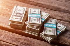Dollar bundles on wooden background. Stock Photos