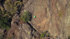 Aerial of Rock Climber Maneuvering up Mountain Cliff on Sunny Day Stock Footage