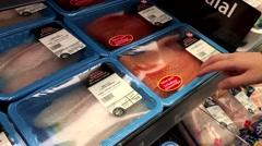 Woman selecting atlantic salmon fillet inside Walmart store at seafood depart - stock footage