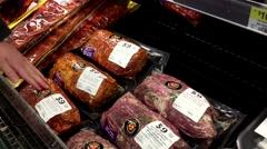 Woman selecting seasoned bonless pork sirloin roast inside Walmart store at m Stock Footage