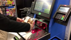 Close up of woman paying foods at self-check out counter inside Walmart store - stock footage