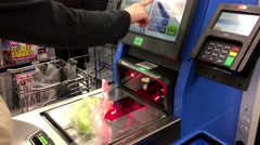 Close up of woman paying foods at self-check out counter inside Walmart store Stock Footage