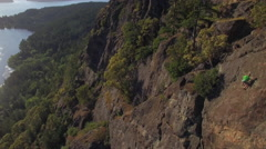 Aerial of Rock Climber on Mountain Cliff with Amazing Scenic View of Ocean Is Stock Footage