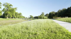 View of a park jogging trail to traffic in the distance 4k Stock Footage