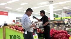 Worker putting onion on sale area inside Walmart store Stock Footage